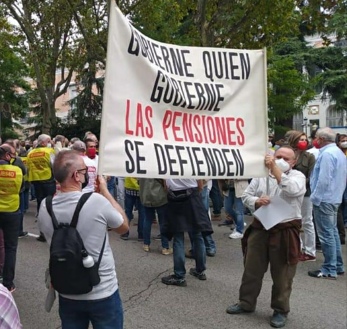 dos hombres sujetan una pancarta en la manifestación por la defensa del sistema público de pensiones