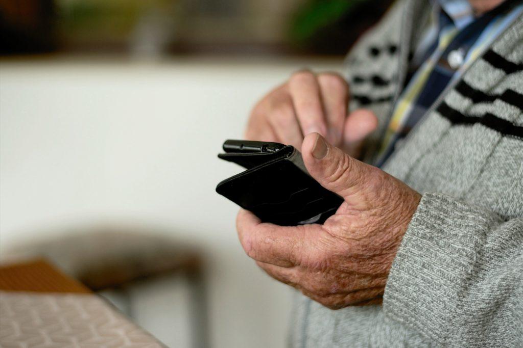 primer plano de un hombre mayor manejando un teléfono móvil; las tecnologías promueven la brecha digital con el colectivo de personas mayores. Hoy, día internacional de las personas mayores, el CEDDD hace hincapié en esa exclusión